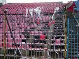 Fragmenty flagii Lecha i połamane krzesełka na sektorze